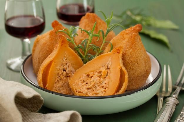 Piatto portoghese coxinhas de frango sul piatto su legno verde