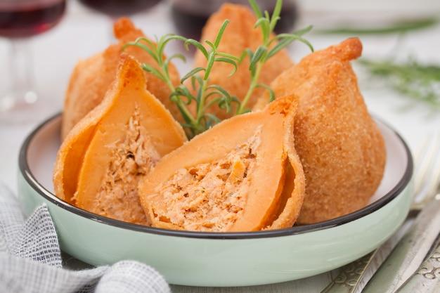 Piatto portoghese coxinhas de frango sul piatto con vino rosso