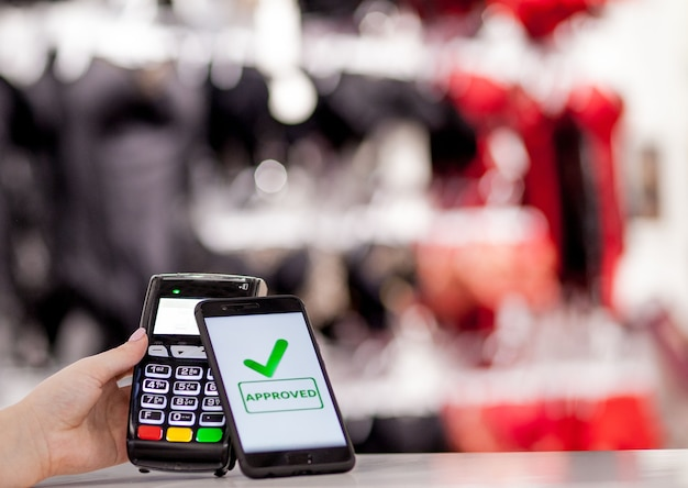 Terminale pos, macchina di pagamento con telefono cellulare in negozio