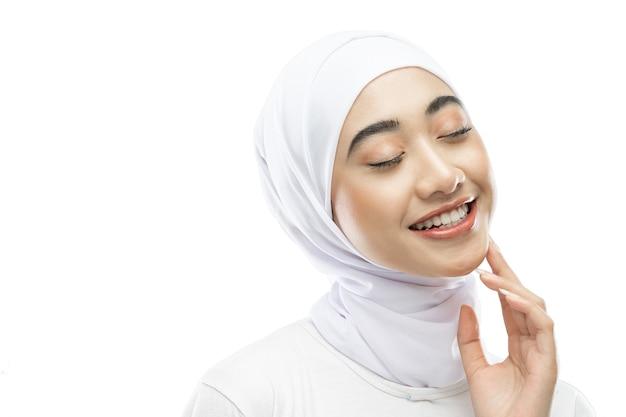 Posa della donna hijab che indossa un velo bianco che sorride e chiude gli occhi