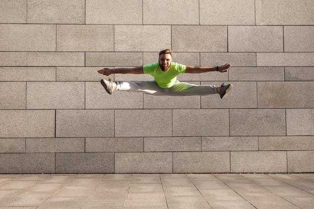 Posa di uno sportivo maschio che salta con le gambe divaricate sullo sfondo grigio della città..