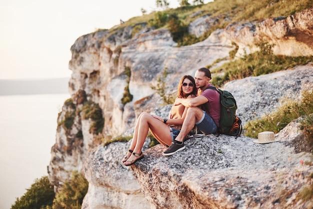 Posa per la foto. giovani coppie che riposano dal camminare sul bordo della montagna. si chiede quanto sia lontana l'altra costa.