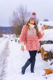 Modello biondo in posa con giacca di pelliccia rosa e cappello viola nella neve. accanto ad alcuni alberi tagliati dal ghiaccio su un sentiero, stile di vita invernale