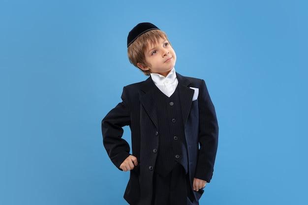 In posa sicuro, carino. ritratto di un giovane ragazzo ebreo ortodosso isolato sulla parete blu. purim, affari, festival, vacanza, celebrazione pesach o pasqua ebraica, ebraismo, concetto di religione.