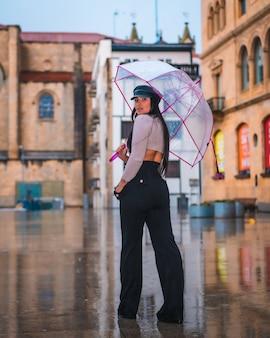 In posa di una giovane bruna latina con un berretto di pelle sotto la pioggia autunnale con un ombrello trasparente in città