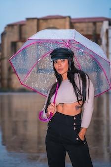 In posa di una giovane latina bruna con un berretto di pelle sotto la pioggia autunnale con un ombrello trasparente