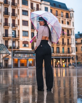 In posa di una giovane latina bruna con un cappello di pelle e pantaloni neri sotto la pioggia autunnale con un ombrello trasparente in città
