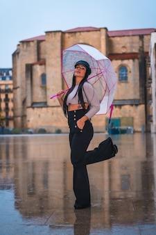 In posa di una giovane latina bruna con un cappello di pelle sotto la pioggia con un ombrello trasparente in città