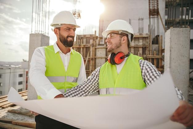 Uomini adulti positivi che leggono il progetto durante i lavori di costruzione