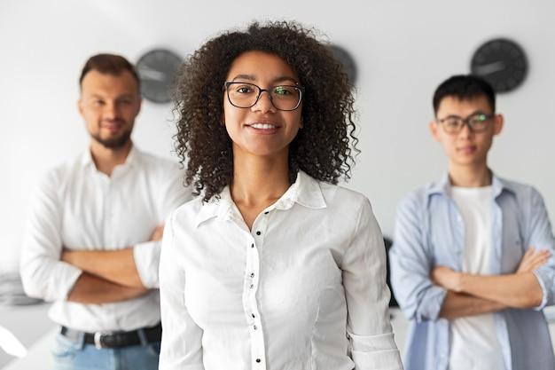 Femmina afroamericana positiva in bicchieri sorridendo e guardando la fotocamera mentre si trovava vicino a diversi colleghi maschi nell'area di lavoro contemporanea