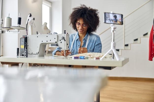 Il sarto da donna afroamericano positivo spara tutorial sul posto di lavoro con la macchina da cucire in studio