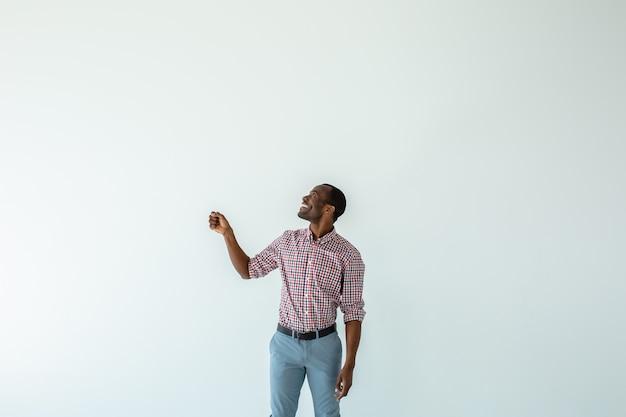 Uomo afroamericano positivo che sorride mentre tiene un ombrello