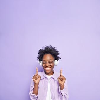 La donna afroamericana positiva con i capelli ricci dei capelli della pelle scura indica sopra