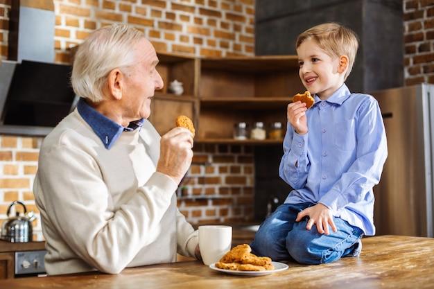 Uomo invecchiato positivo che mangia biscotti fatti in casa con suo nipote