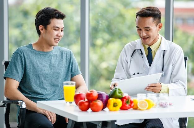Medico asiatico positivo che sorride e mostra il tavolo al paziente di sesso maschile mentre è seduto alla scrivania con cibo sano in clinica