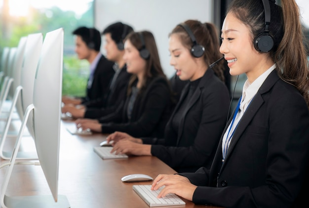 Positivo asian female customer services agente con auricolare che lavora in un call center