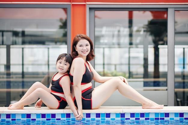 Madre asiatica positiva e figlia che si siedono sul bordo della piscina, tenendosi per mano e sorridendo