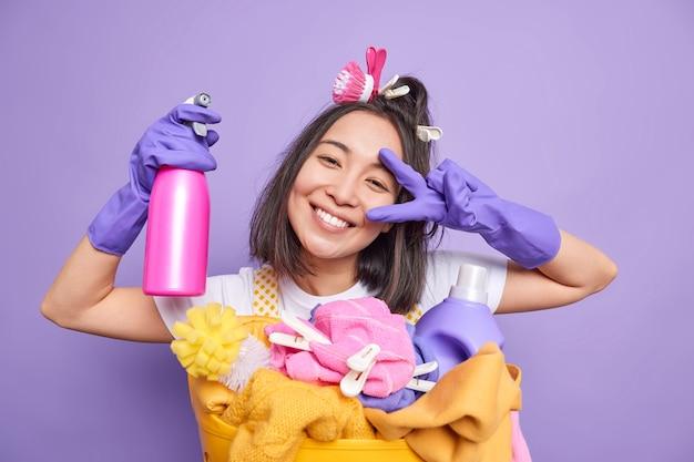 La donna asiatica positiva inclina la testa sorride felicemente e fa un gesto di pace tiene lo spray detergente fa il bucato durante il tempo libero ha molto lavoro sulle faccende domestiche