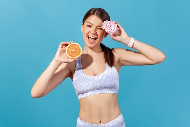Donna atletica positiva che tiene metà di pompelmo succoso maturo e ciambella rotonda con glassa rosa