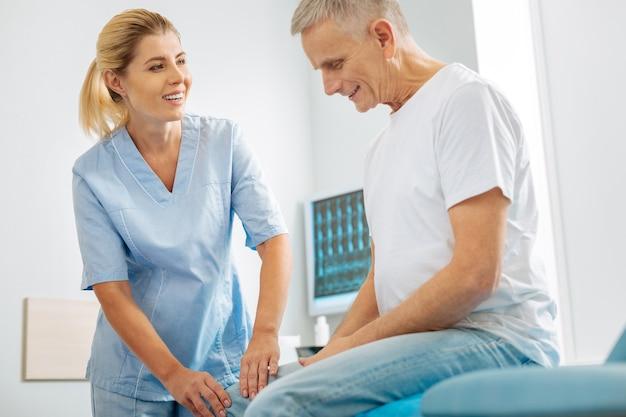 Attitudine positiva. felice abile terapista piacevole che sorride e parla al suo paziente mentre controlla la sua gamba
