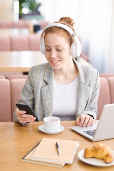 Ragazza studentessa attraente positiva in cuffie wireless seduto al tavolo in un ristorante moderno e chiacchierando con il ragazzo online mentre si prepara per l'esame