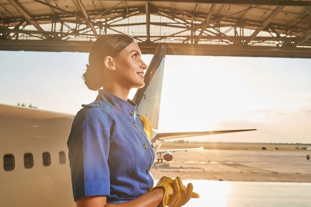 Bella hostess di compagnia aerea positiva in uniforme blu e gialla in piedi in un hangar in una giornata di sole e guardando in alto con un sorriso