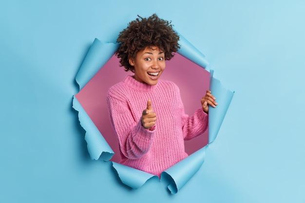 La bella donna etnica riccia positiva ti fa ottenere questo gesto elogia i buoni punti di lavoro a te incoraggia la persona sorride indossa volentieri il maglione lavorato a maglia sfonda il muro di carta blu