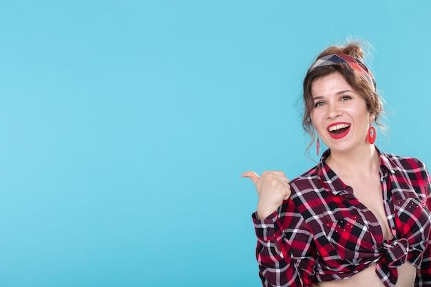 Bella giovane donna positiva in una camicia vintage a quadri guardando la telecamera e sorridente in posa