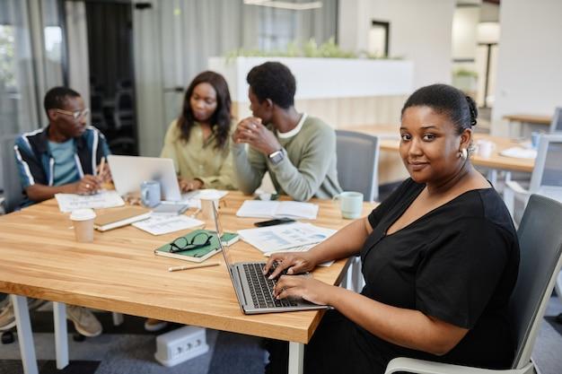Imprenditrice nera positiva che lavora al computer portatile quando i suoi colleghi hanno una sessione di briefing