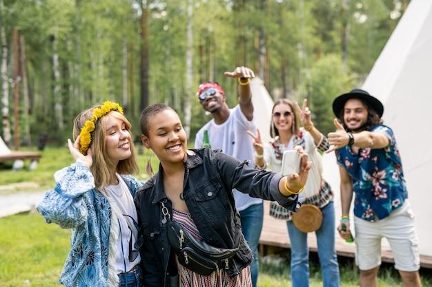 Donna nera positiva con orecchini lunghi che fotografa con un amico in corona sullo smartphone mentre i loro amici fanno gesti freddi in background