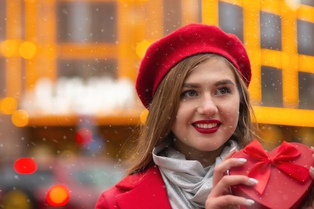 La donna bionda positiva indossa un berretto rosso e un cappotto che tiene in mano una scatola regalo a forma di cuore sullo sfondo delle luci del bokeh. spazio per il testo