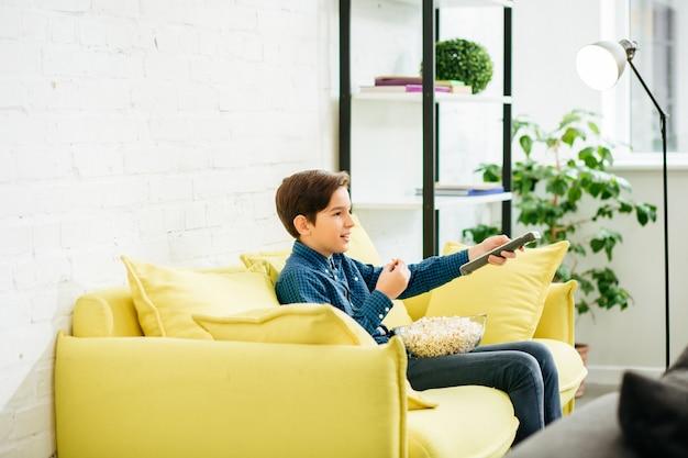 Ragazzo positivo che utilizza il telecomando e cambia i canali tv mentre è seduto sul divano giallo con una ciotola di popcorn sulle ginocchia