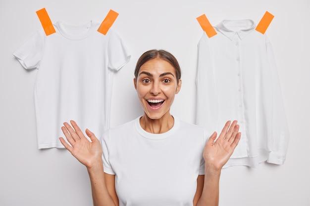 La donna caucasica castana positiva sorride ampiamente mostra i denti solleva le palme pose contro il muro bianco con vestiti intonacati che sono di buon umore