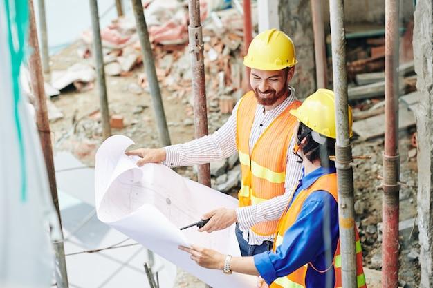 Costruttori positivi in elmetti protettivi gialli che controllano il progetto di costruzione e discutono del piano o dei lavoratori