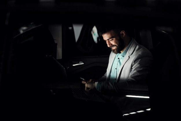 Uomo d'affari positivo che finisce il suo lavoro straordinario che lavora fino a tardi.