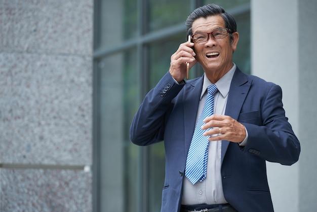 Uomo d'affari positivo che fa telefonata