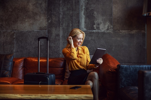 Imprenditrice positiva seduta in una hall di un hotel e il check-in in un hotel online. è in viaggio d'affari. telecomunicazioni, viaggi, viaggi d'affari