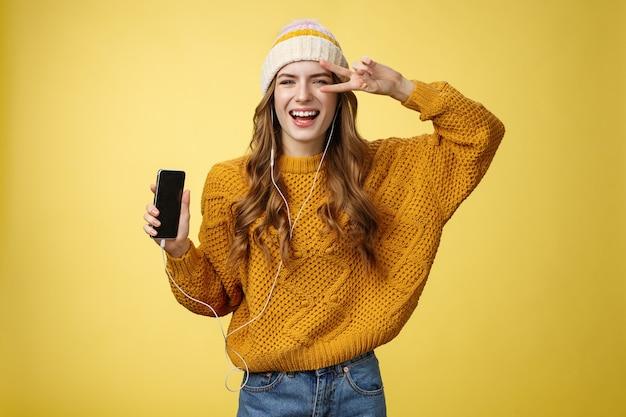 Positiva spensierata affascinante ragazza mostra gesto di pace indossando auricolari cablati che mostrano lo schermo dello smartphone che promuove l'app cool nuovissimo telefono cellulare, ridendo spensierato sfondo giallo