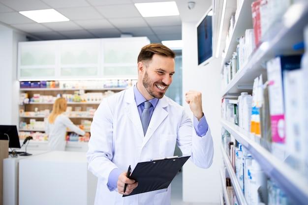 Farmacista caucasico positivo in piedi dallo scaffale con farmaci in farmacia.