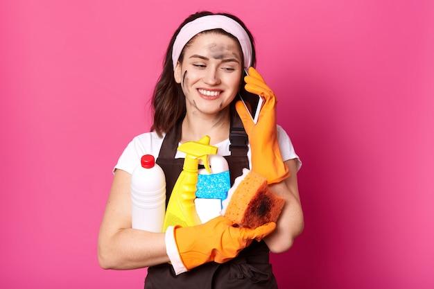 Donna caucasica positiva che parla sul telefono cellulare mentre puliva la sua casa, tenendo in mano spugna e detersivi, vestita in abiti casual, indossa guanti di gomma e grembiule, isolato sopra il muro rosa.
