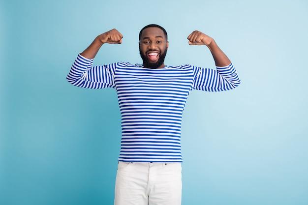 Positivo allegro sorpreso ragazzo afro americano mostra i muscoli ottenere bodybuilding allenamento acqua spiaggia primavera vacanza sport pratica indossare pantaloncini gilet nautico bianco isolato parete di colore blu