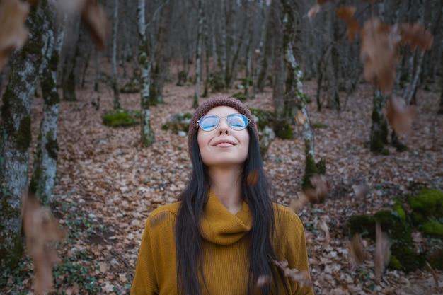 La donna allegra positiva gode dell'autunno nel parco o nei boschi indossa un pullover giallo e un cappello, occhiali. ragazza hipster felice di umore nel viaggio su strada nel tardo autunno nella foresta