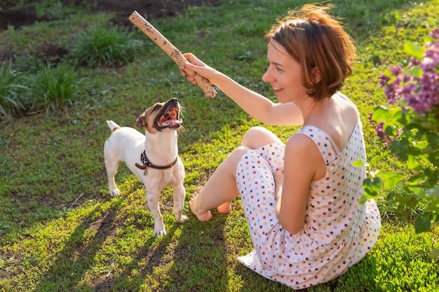 Positiva donna allegra che gioca con il suo amato cane jack russell terrier nel cortile della sua casa di campagna in una soleggiata giornata estiva. concetto di amore per gli animali e ricreazione familiare.