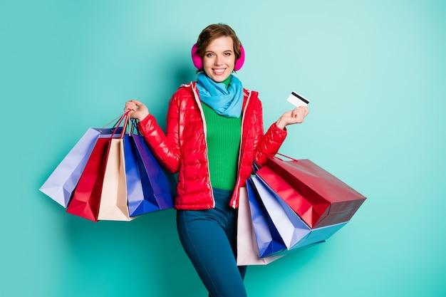 Positivo donna allegra shopping addicted funky hipster acquistare tenere molte borse pagare con carta di debito indossare tuta sportiva rosa rossa maglione verde pantaloni blu pantaloni isolato muro colore turchese