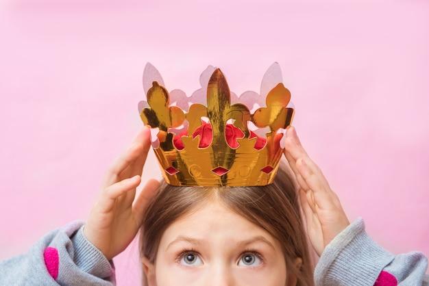 La ragazza positiva del bambino prova una corona sulla sua testa