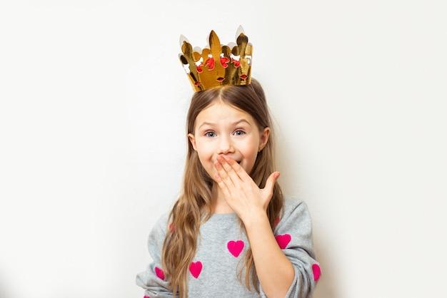 La ragazza del bambino positivo con una corona copre timidamente la bocca