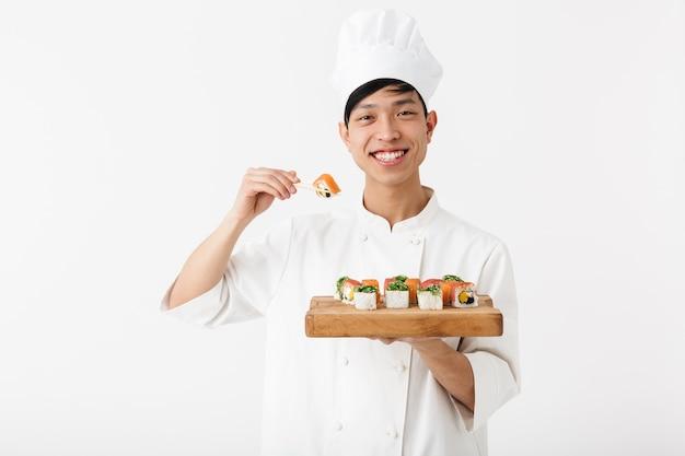 Uomo capo cinese positivo in uniforme da cuoco bianco tenendo il piatto e mangiare sushi con le bacchette isolate sul muro bianco