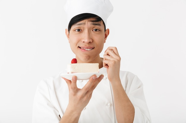 Uomo capo cinese positivo in uniforme bianca del cuoco che sorride alla macchina fotografica mentre tiene il piatto con una gustosa cheesecake isolata sopra la parete bianca