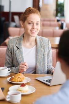 Positivo fiducioso giovane femmina specialista di marketing con i capelli rossi seduto al tavolo nella caffetteria e spiegando la strategia pubblicitaria al cliente alla riunione informale