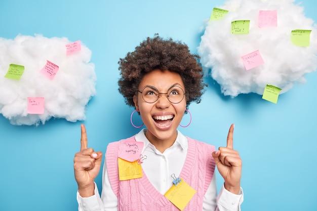 La donna dai capelli ricci positiva punta il dito indice sulle nuvole con adesivi colorati indossa occhiali rotondi mostra piani e informazioni per ricordare isolato su muro blu